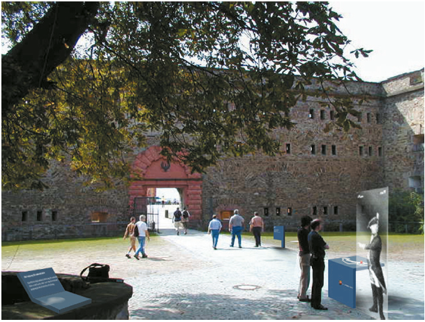 Durchgang zum Hauptplatz der Festung mit verschiedenen Infoelementen, darunter Lageplan mit Standort, Hinweisschild und historischen Hintergrundinformationen.
