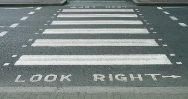 Ein Straßenübergang in London. Manchmal ist es hilfreich, wenn Symbole mit zusätzlichen textuellen Aufforderungen ergänzt werden.